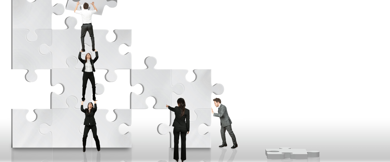 Menschen bauen übergroßes Puzzle zusammen